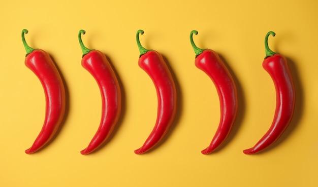 Fünf scharfe rote paprikaschoten auf einem gelben