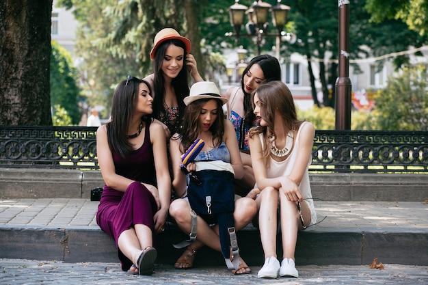 Fünf schöne junge frauen betrachten die tasche im park