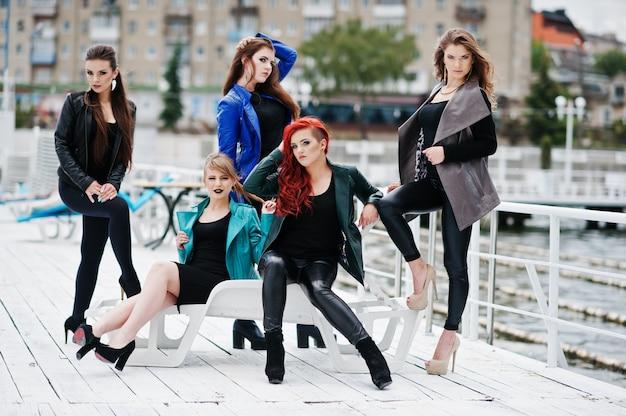 Fünf schöne modelle der jungen mädchen an den lederjacken, die auf liegeplatz aufwerfen.