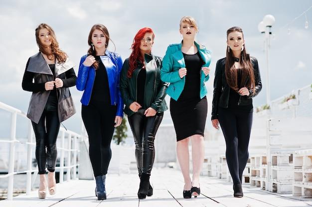 Fünf schöne modelle der jungen mädchen an den lederjacken, die auf pier aufwerfen