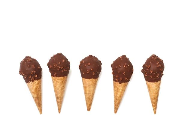 Fünf schokoladeneistüten mit mandelchips an einer weißen wand