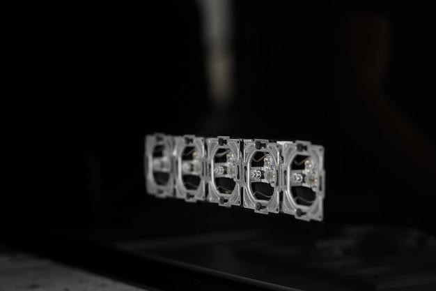 Fünf steckdosen in reihe, zerlegt und in schwarze glaswand montiert