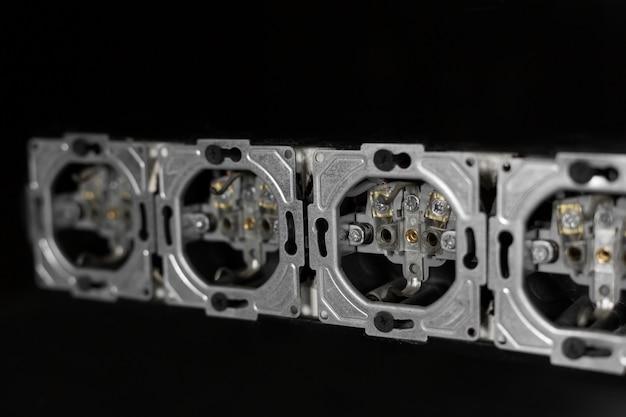 Fünf steckdosen in reihe, zerlegt und in schwarze glaswand montiert.