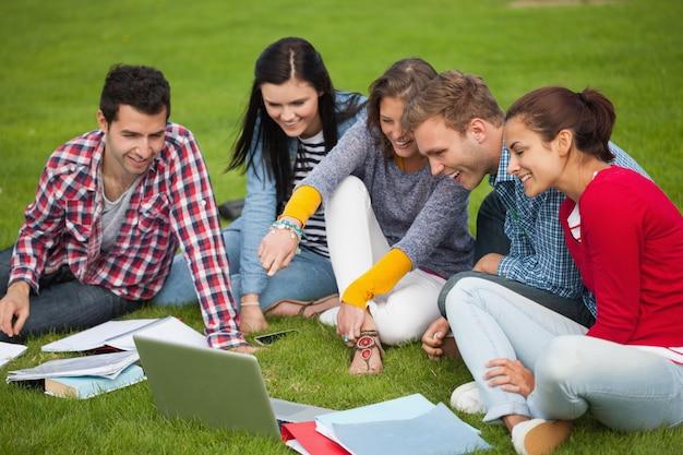 Fünf studenten, die auf dem gras zeigen auf laptop sitzen