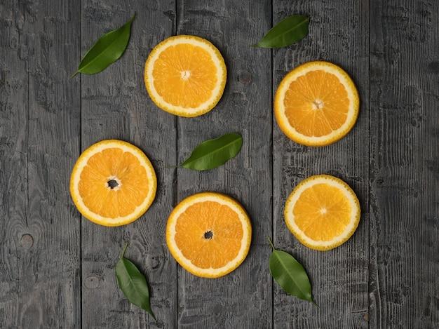 Fünf stücke orange und grüne blätter auf einem hölzernen hintergrund. flach liegen.