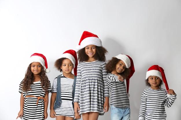 Fünf süße afrikanische mädchen in gestreifter kleidung und weihnachtsmützen auf weißem hintergrund