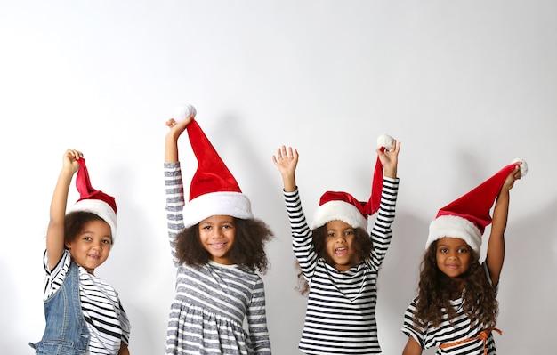 Fünf süße afrikanische mädchen in gestreifter kleidung und weihnachtsmützen