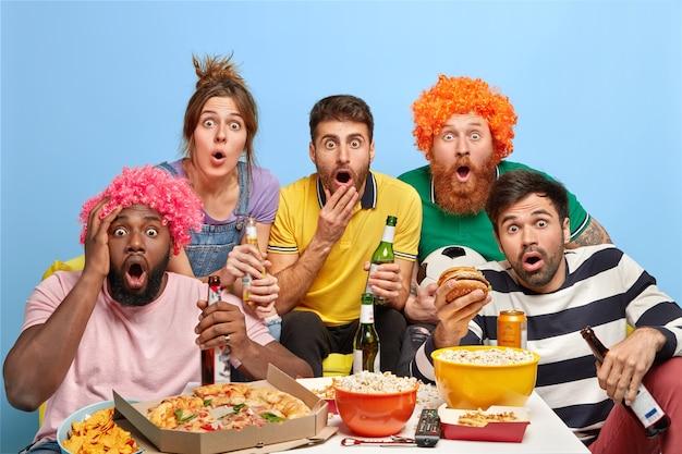 Fünf verschiedene freunde starren geschockt auf den fernseher