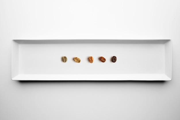 Fünf verschiedene sorten gerösteter kaffeebohnen, aromatisch, von roh bis vollständig geröstet, isoliert auf draufsicht auf weißem teller