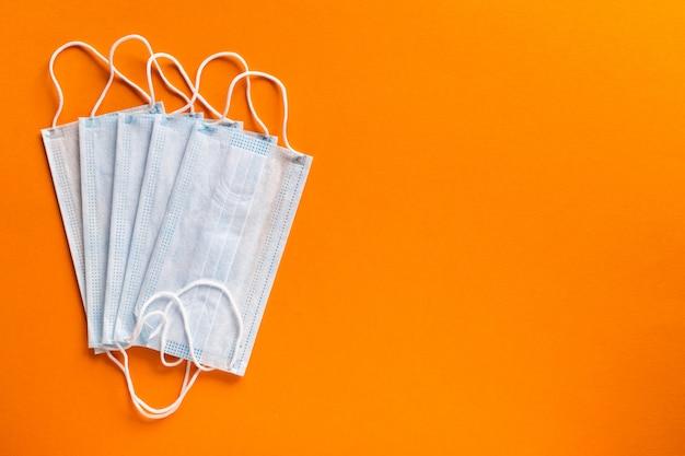 Fünf weiße medizinische masken auf einem orangefarbenen hintergrund