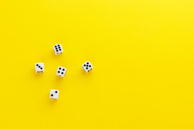 Fünf würfel, die verschiedene seiten auf gelbem hintergrund zeigen. würfel mit zahlen spielen. artikel für brettspiele. flache lage, draufsicht mit kopierraum.