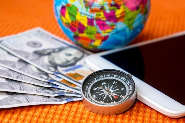 Fünfhundert us-dollar, kompass, erdkugel und digitales tablet. reisekonzept.