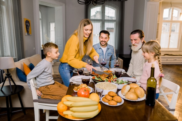 Fünfköpfige familie, großvater, eltern und kinder, die am tisch sitzen und gebratenen truthahn essen gehen, während die glückliche mutter den truthahn schneidet