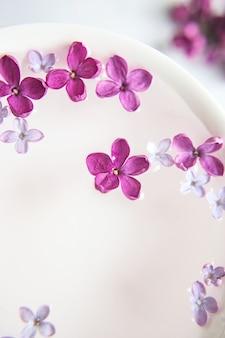 Fünfzackige lila blume unter lila blumen in einer tasse mit wasser. platz für text aufräumen. lila zweig mit einer blume mit 5 blütenblättern.