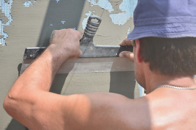Fünfzig jahre alte manuelle arbeitskraft mit der wand, welche die werkzeuge erneuern haus vergipsen