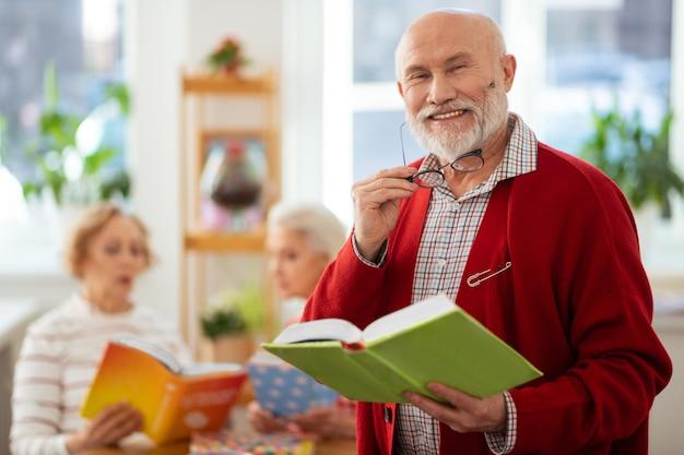 Für besseres sehen. netter alter mann, der seine brille aufsetzt, während er sich darauf vorbereitet, das buch zu lesen?