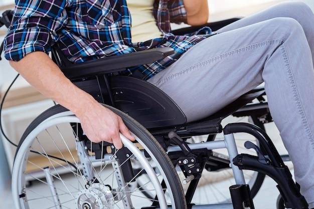 Für bewegungen. ungültiger bürger, der auf beweglichem stuhl sitzt, während er zu hause arbeitet