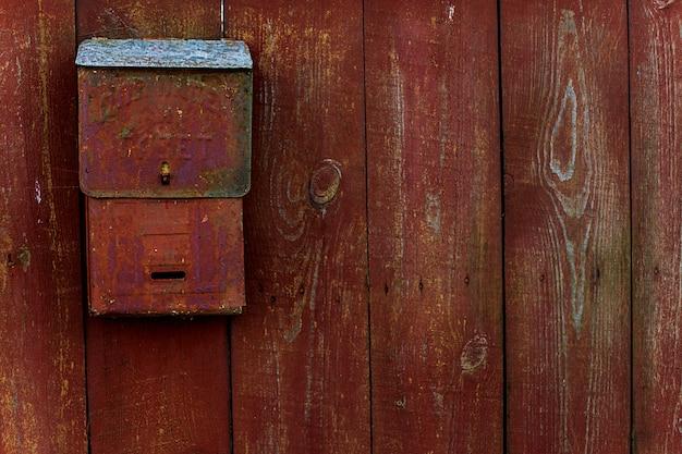 Für briefe und zeitungen. übersetzung des russischen textes. briefkasten auf dem holzzaun rot