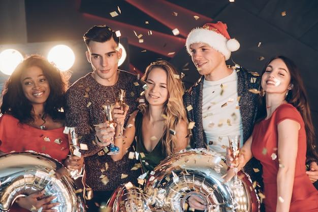 Für das bild posieren. foto der firma von vier freunden, welche die party mit alkohol haben