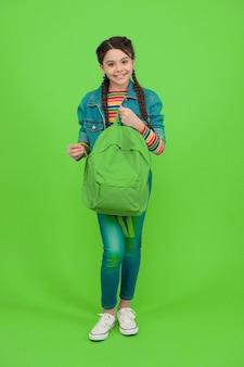 Für das fernweh in dir. glückliches kind halten rucksack grünen hintergrund. reisen und fernweh. wandern und entdecken. fernweh-konzept. sommerurlaub. abenteuer und entdeckung. schulferien.