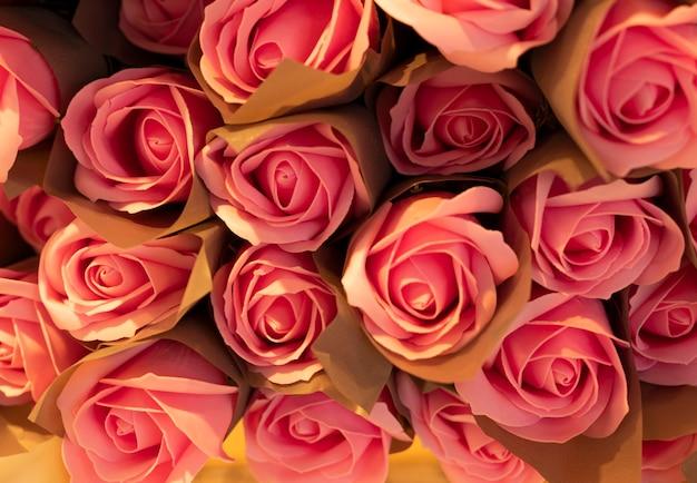 Für den hintergrund sind zahlreiche rosensträuße in süßen farben in einem weichen und verschwommenen stil aneinandergereiht