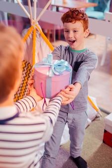 Für dich. positiv entzücktes kind, das ein lächeln auf seinem gesicht behält und mit seinem freund kommuniziert