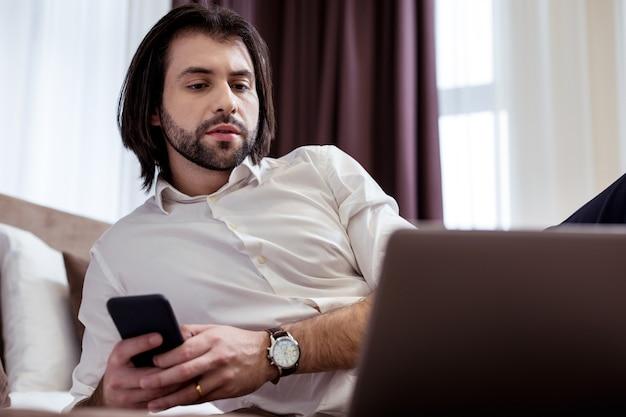 Für die arbeit. intelligenter gutaussehender mann, der moderne technologische geräte verwendet, während er fern arbeitet