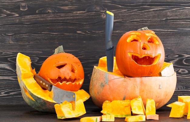 Für die feier der orangefarbenen farbe des halloween-feiertags kürbis geschnitzt, liegen sie auf einer schwarzen holzoberfläche auf einer schwarzen holzwand