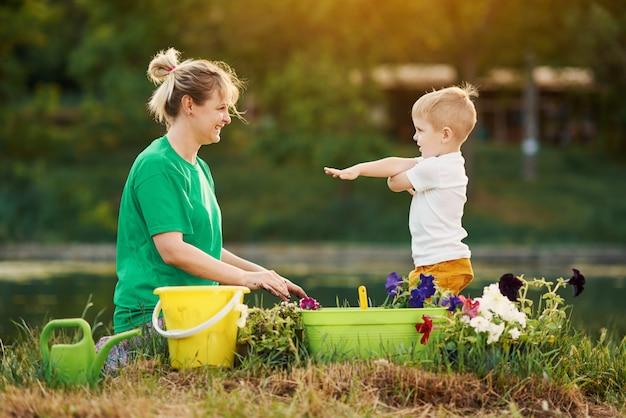 Für die natur sorgen. mutter und sohn pflanzen sämling im boden auf zuteilung am flussufer. botanisches und ökologisches konzept.