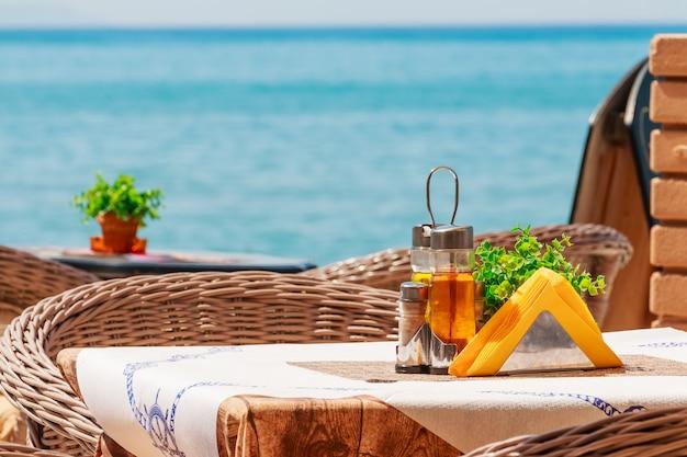Für einen tisch im restaurant gedeckt. gewürze, öl, servietten, zahnstocher. service im restaurant in der nähe des meeres. summer seaside restaurant terrasse oder veranda interieur, holzmöbel, meerblick. freizeitkonzept