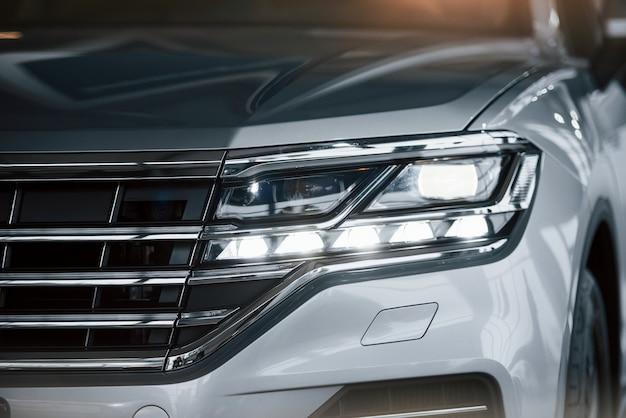 Für erfolgreiche menschen. partikelansicht des modernen weißen luxusautos, das tagsüber drinnen geparkt wird