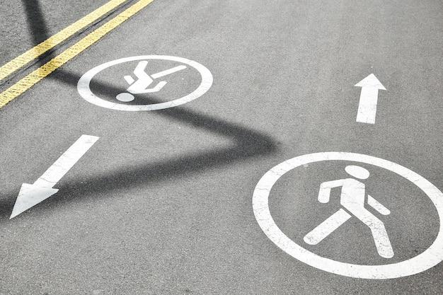Für fußgänger reservierte fahrspuren. asphaltstraße mit fußgängerzone. weißes schild am boden. erholungsgebiet im stadtpark. straßenschilder