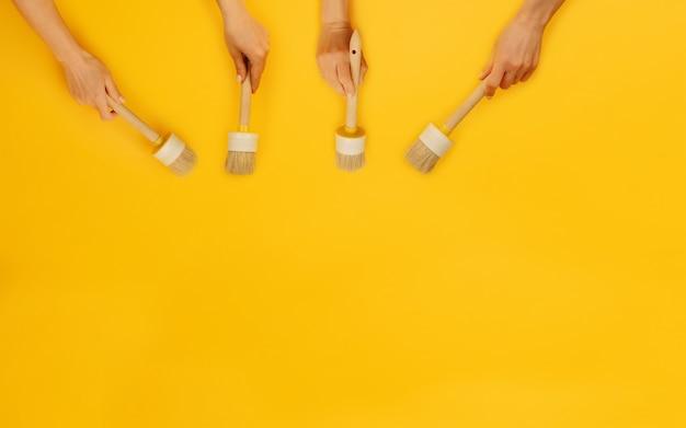 Für hände, die pinsel auf gelbem hintergrund mit kopienraumkonzept der kreativitätsverbesserung halten ...