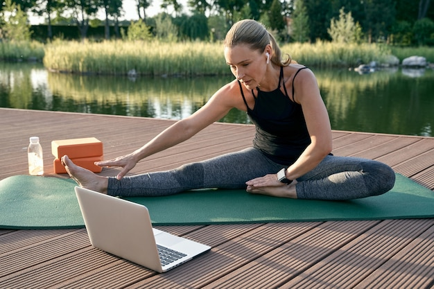 Für ihren inneren frieden sieht sportlich schöne frau tutorial auf einem laptop an, während sie yoga auf einer matte machen