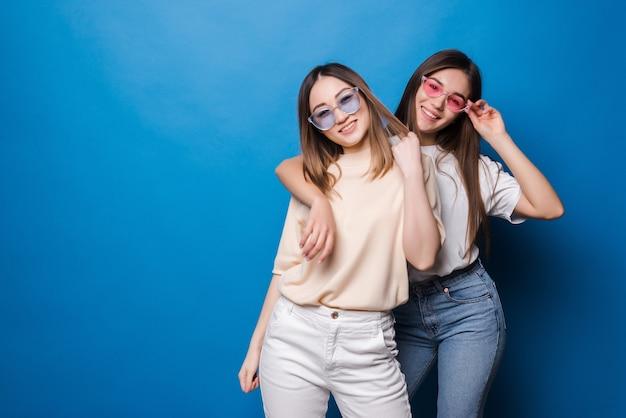 Für immer freunde. zwei niedliche reizende freundinnen in der sonnenbrille, die mit lächeln auf blaue wand lokalisiert aufwirft
