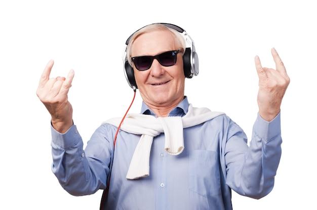 Für immer jung. fröhlicher älterer mann mit kopfhörern, der musik hört und handzeichen zeigt, während er vor weißem hintergrund steht