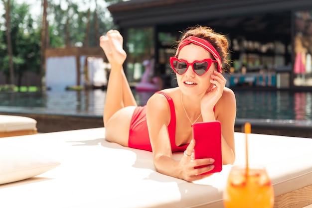 Für soziale medien. nette freudige frau, die auf dem strandbett liegt, während sie fotos von sich selbst macht