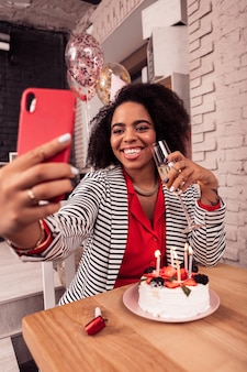 Für soziale netzwerke. glückliche freudige frau, die fotos auf ihrem telefon macht, während sie sie im internet veröffentlichen möchten