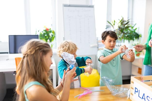 Für zukünftiges recycling. schuljungen und ihre schöne klassenkameradin halten plastikflaschen für das zukünftige recycling