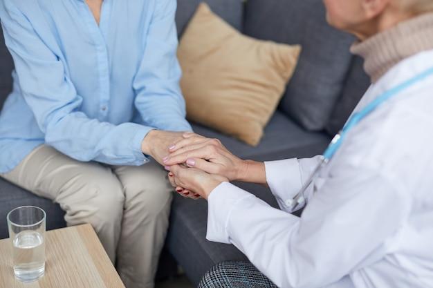 Fürsorgliche ärztin, die hände mit patient hält