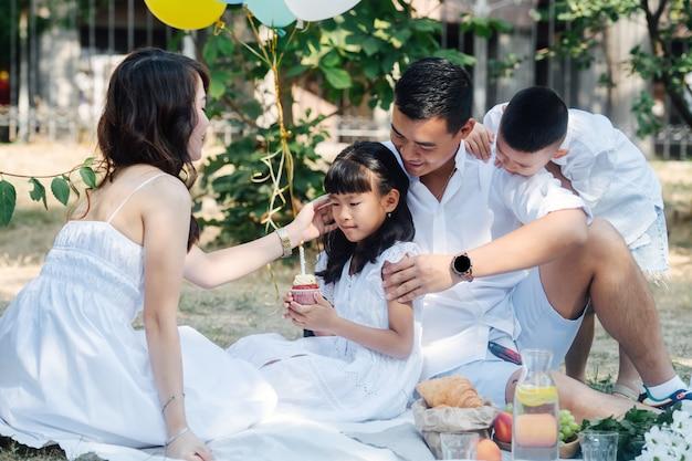 Fürsorgliche asiatische familie, die den geburtstag ihres kleinen mädchens in einem park mit einem kleinen kuchen feiert. eltern und ihre kinder in weißer kleidung in einem baumschatten.