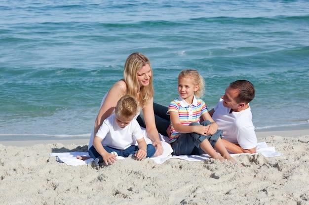 Fürsorgliche eltern mit ihren kindern, die auf dem sand sitzen