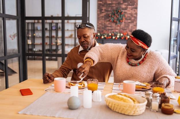 Fürsorgliche frau. glückliche nette frau, die sich um ihren ehemann kümmert, während schlagsahne auf seine toasts setzt