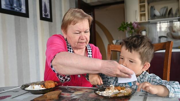 Fürsorgliche großmutter mit ihrem enkel essen.