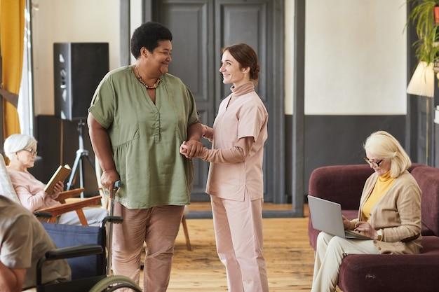 Fürsorgliche krankenschwester hilft senioren im altersheim