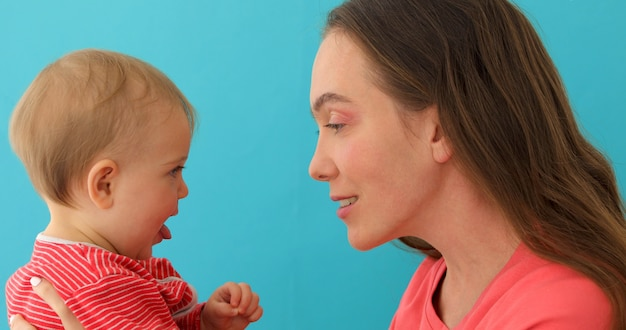 Fürsorgliche mutter, die mit glücklichem kleinem baby spielt