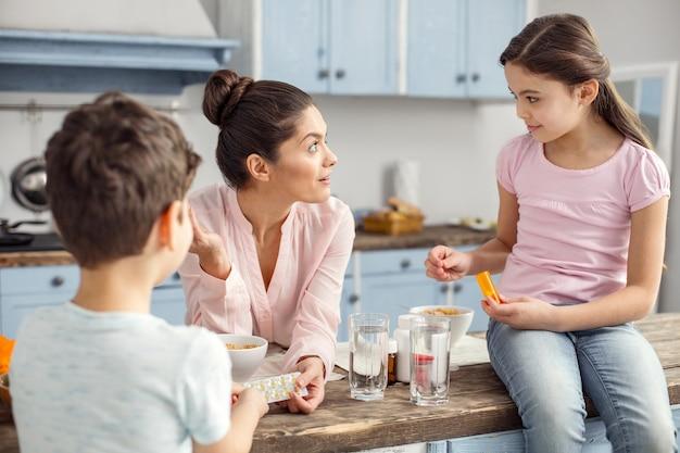 Fürsorgliche mutter. lächelnde liebevolle dunkelhaarige junge mutter, die vitamine hält und mit ihren kindern und dem mädchen spricht, das auf dem tisch sitzt und die familie, die gesundes frühstück hat