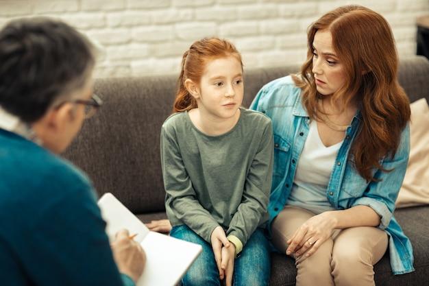 Fürsorgliche mutter. nette junge frau, die ihre tochter anschaut, während sie ihr zuhört
