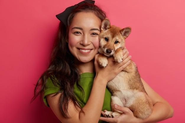 Fürsorgliche weibliche gastgeber posiert mit stammbaum niedlichen hund, froh, welpen zu kaufen, verbringt gerne freizeit mit haustier, drückt liebe aus