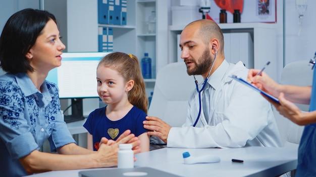 Fürsorglicher arzt, der mädchen im büro mit stethoskop berät, das den atem überprüft. facharzt für medizin, der das gesundheitswesen anbietet beratung diagnostische untersuchung behandlung im krankenhausschrank